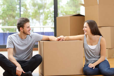 Happy couple looking at each other moving to new home surrounded by boxes sitting on the floor