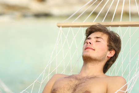 Relaxed shirtless man sunbathing resting on a hammock by the beach