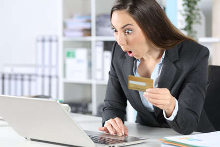 Surprised executive woman pays online with credit card on laptop sitting on a desk at office Stockfoto