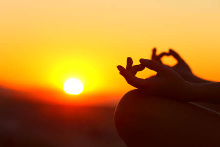 Close up of woman hands silhouette doing yoga relaxing at sunset outdoor