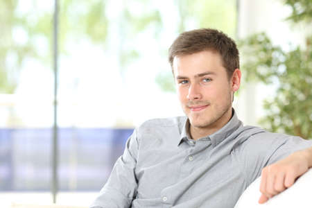 Portrait of a young man looking at camera posing sitting in the sofa at home