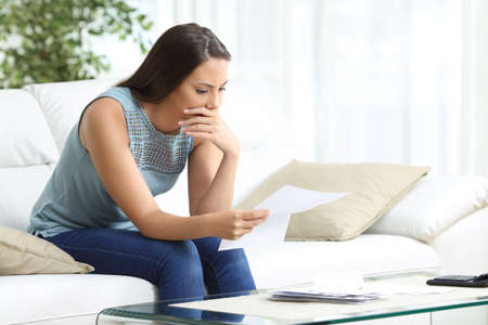 Worried woman reading lettter sitting on the sofa in the living room at home Stock Photo