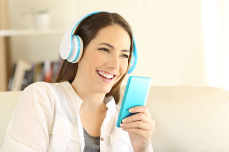 Happy woman listening to music using blue phone sitting on a sofa in the living room at home Foto de archivo