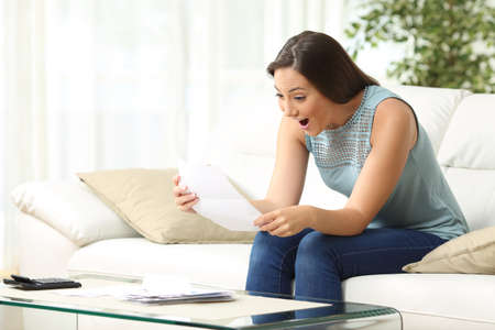 Excited woman reading good news in letter sitting on the sofa in the living room at home