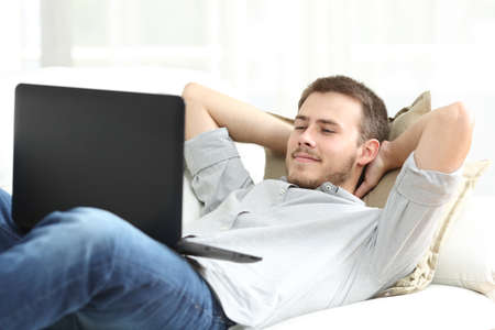 Relaxed man watching video on laptop lying on the sofa in the living room at home