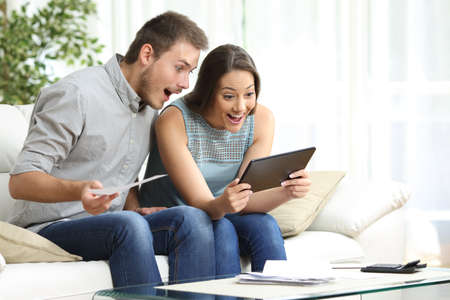 Excited couple checking tablet and receipts sitting on the sofa in the living room at home