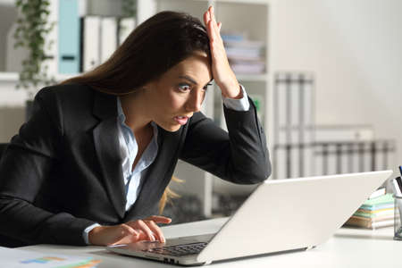Surprised executive woman discovering mistake on laptop sitting on a desk at office