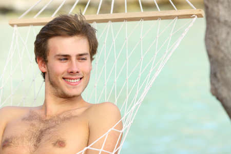 Happy shirtless man looking away relaxing lying on a hammock on the beach