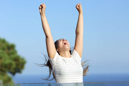 Excited woman celebrating vacation raising arms in a hotel balcony on the beach