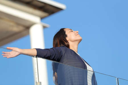Renter woman breathing fresh air in an apartment balcony on summer vacation Standard-Bild
