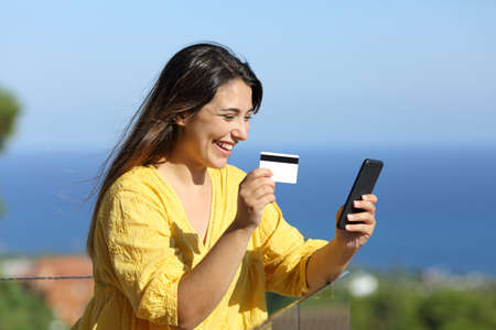 Happy woman buy online with smart phone and credit card in a balcony on the beach