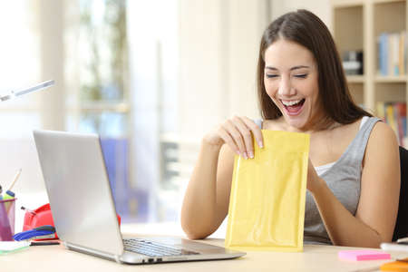 Excited student woman opening and looking inside a padded envelope sitting on a desk at home