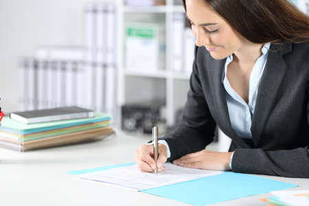 Executive woman filling out form sitting on a desk at the office Standard-Bild