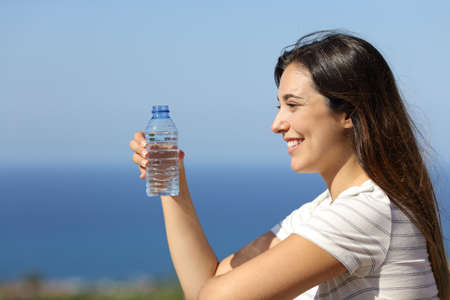Happy woman holds bottled water in a hotel balcony on the beach on summer vacation