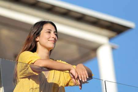 Satisfied woman in yellow contemplating views in a balcony on summer Standard-Bild