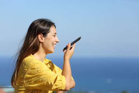 Profile of a happy woman using voice recognition on smart phone in a hotel balcony on the beach on summer vacation Standard-Bild - 153717166