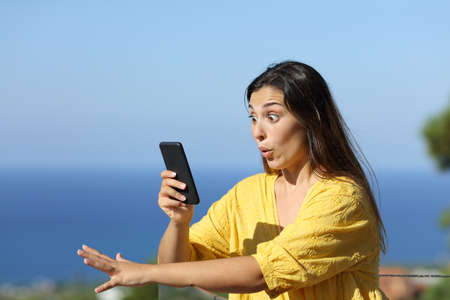 Surprised woman checks smart phone in a hotel balcony on the beach on summer vacation