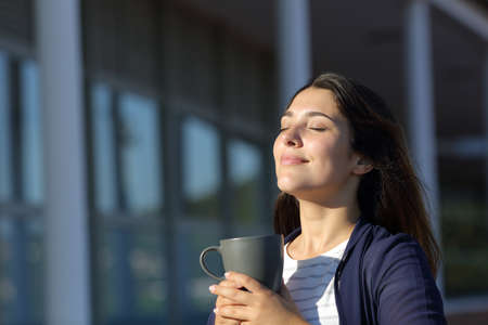 Woman relaxing drinking coffee and breathing fresh air in a hotel