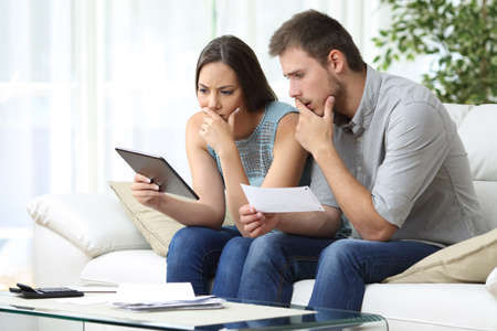 Worried couple comparing receipt on tablet sitting in the sofa in the living room at home Standard-Bild