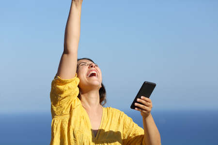 Excited woman in yellow celebrating good news holds smart phone on the beach on vacation