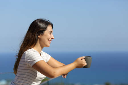 Side view portrait of a happy woman drinking coffee in a hotel balcony on the beach on summer vacation