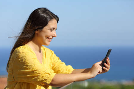 Happy woman using smart phone in a hotel balcony on the beach Standard-Bild - 154663608