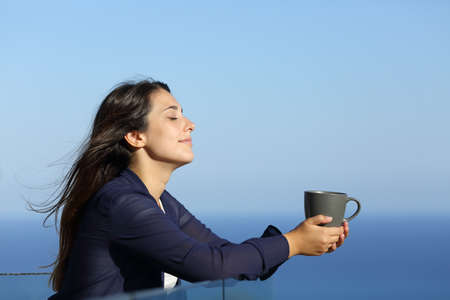 Woman relaxing breathing fresh air holding coffee cup in a hotel balcony on the beach on summer vacation Standard-Bild