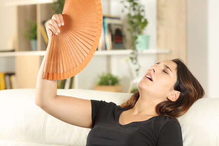 Girl suffering heat stroke fanning sitting on a sofa in the living room at home