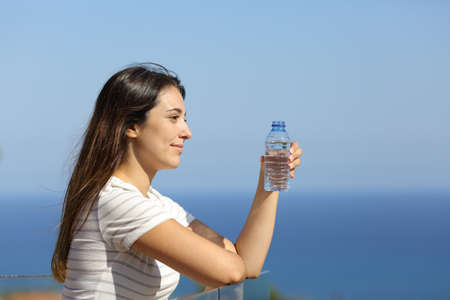 Profile of a woman holding a bottle of water looking away in a hotel balcony on the beach on summer vacation Standard-Bild - 154663712