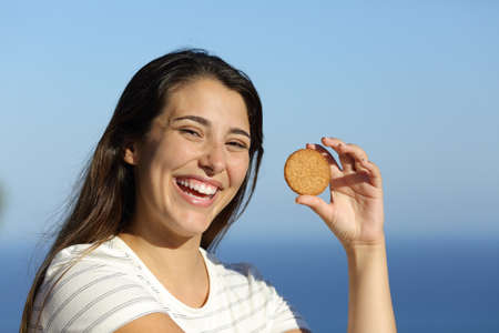 Happy woman showing cookie laughing on the beach a sunny day