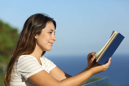 Profile of a woman reading a book in a hotel balcony on the beach on summer vacation