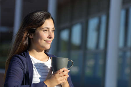 Woman drinks coffee in a terrace looking away a sunny day