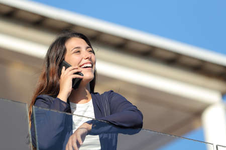Happy apartment owner calling on phone looking away in a balcony
