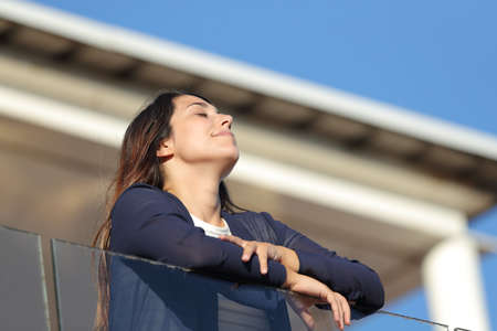 Renter breathing fresh air in an apartment balcony on summer holiday