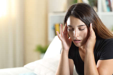 Woman suffering migraine complaining sitting on a sofa in the living room at home