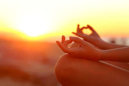 Close up of woman hands stress relieving doing yoga exercise at sunset outdoor