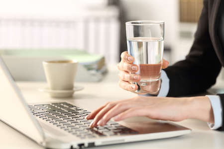 Close up of a executive woman hands holding water glass using laptop sitting on a desk at office