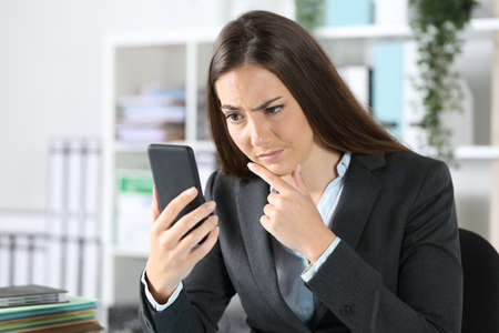 Suspicious executive woman checking smart phone sitting on a desk at the office Standard-Bild