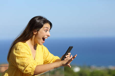 Shocked woman in yellow reads exciting news on smart phone in a hotel balcony on the beach on summer vacation