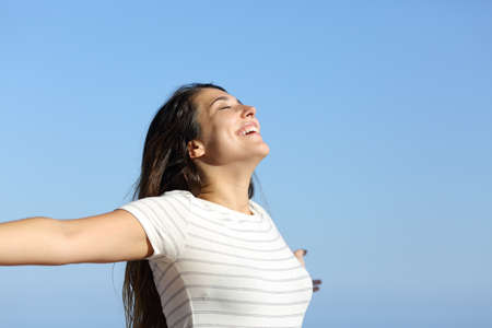 Happy woman breathing fresh air and spreading on the beach with a blue sky in the background