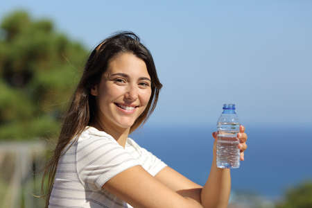 Happy woman holding a bottle of water looks at you in a balcony on the beach Standard-Bild