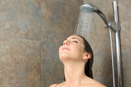 Satisfied woman having shower relaxing with water falling on head on a bathroom Standard-Bild - 154629528