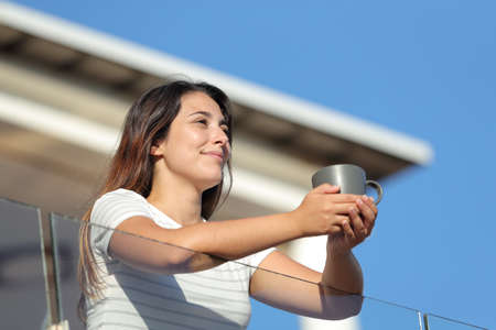 Guest woman holding coffee cup contemplating views from apartment balcony on summer