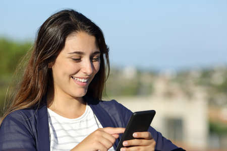 Happy woman checking smart phone outdoors a sunny day Standard-Bild