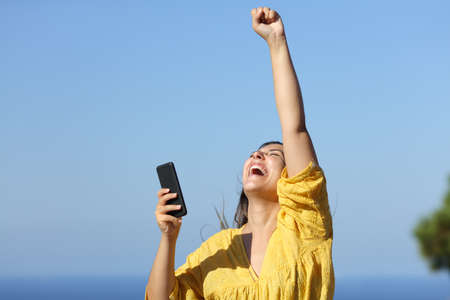 Excited woman celebrating success holds smart phone on the beach