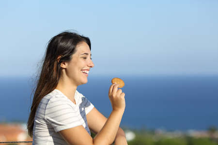 Portrait of a happy woman eats cookie in a hotel balcony on the beach