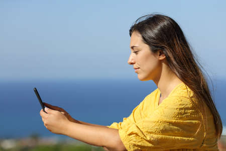 Side view portrait of a serious woman using phone in a hotel balcony on summer vacation