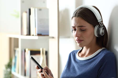 Sad teen complaining listening to music looking down and crying at home