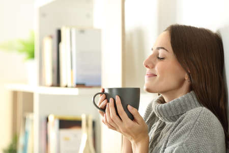 Side view portrait of a satisfied woman smelling coffee wearing sweater in winter at home