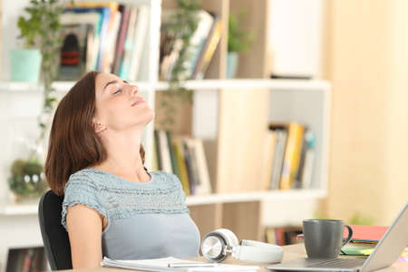 Relaxed student breathing deeply fresh air sitting at home